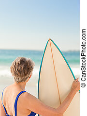 Woman with her surfboard at the beach