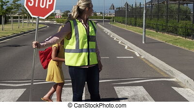 Caucasian woman wearing high visibility vest, holding stop sign, standing on pedestrian crossing, Caucasian girl riding scooter and crossing road, slow motion. Elementary school children, road safety.