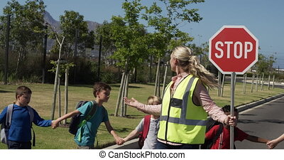 Caucasian woman wearing high visibility vest, holding stop sign, standing on a pedestrian crossing, multi-ethnic group of children crossing road, slow motion. Elementary school children, road safety.