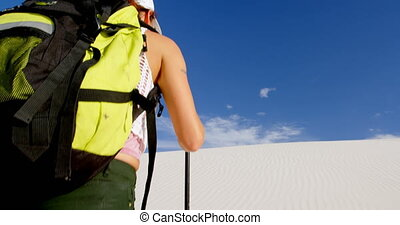 Woman with hiking pole walking in the desert 4k - Woman with...