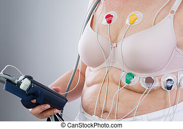 Woman with holter monitor device for daily monitoring of electrocardiogram and blood pressure