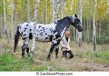 Woman with horse in a birch forest