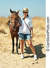 Woman with horse on the beach