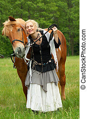 Woman in boho style with horse on meadow