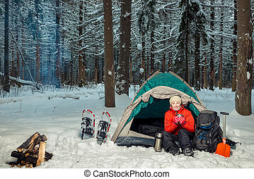 woman with hot tea in a tent in a winter forest