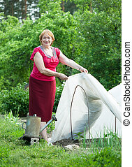Woman with hothouse at   garden