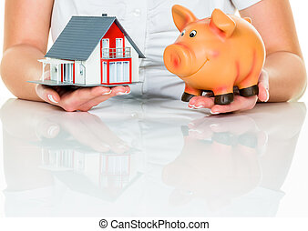woman with house and piggy bank - a woman with a house and a...