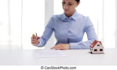 woman with house model and pen signing contract -...