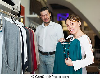 Woman with husband choosing clothes