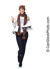 Full length of smiling young woman wearing warm hat and scarf carrying a pair of ice skates and gesturing thumb up, over white background