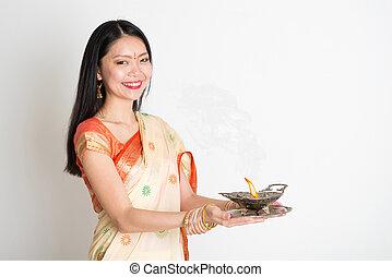 Woman with Indian sari dress holding oil lamp