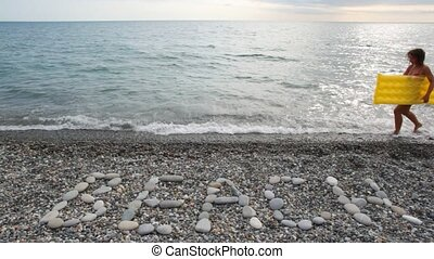 woman with inflatable mattress walking on beach, BEACH inscription in foreground