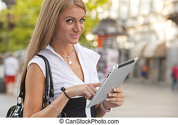 Woman with iPad tablet computer walking on urban street