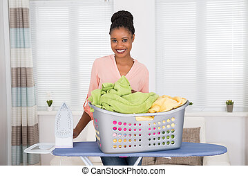 Smiling Young African Woman With Iron And Basket Full Of Clothes