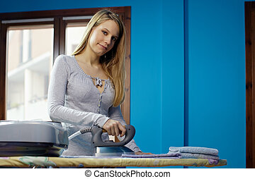 woman with iron doing chores