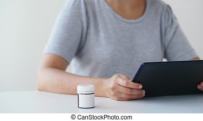 woman with jar of medicine pills and tablet pc