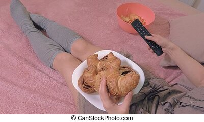 Woman with junk food near Tv