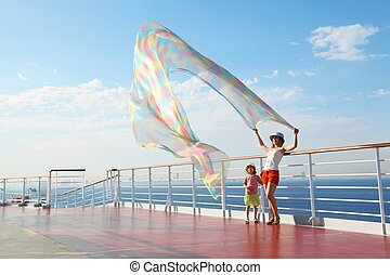 woman with kerchief standing on deck of cruise ship. her...