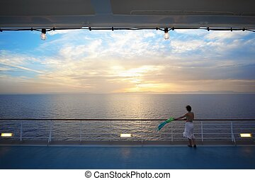 woman with kerchief standing on deck of cruise ship and looking away. sunset.