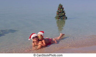 Woman with kid in red Santa hats enjoying Christmas vacation lying in surf