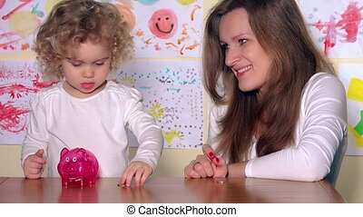 woman with kid putting coins in piggy bank and show finger up looking at camera