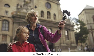 Woman with kid tourists capturing themselves with small personal camera