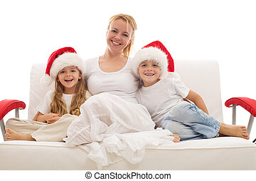 Woman with kids sitting on a sofa at christmas time