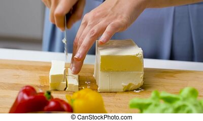 woman with knife chopping feta cheese on board - healthy ...