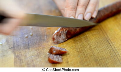 Woman with knife cutting smoked sausage in the kitchen.