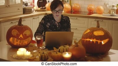 Woman with laptop amidst Halloween decorations