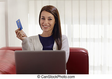 woman with laptop and credit card shopping on internet -...
