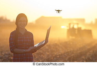 Woman with laptop and drone on field