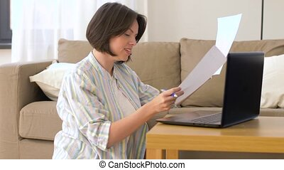 woman with laptop and papers at home - accounting,...