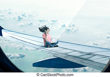 Woman with laptop and phone sitting on plane wing