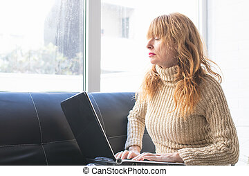 woman with laptop at home with expression of tiredness or boredom
