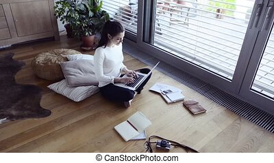 Woman with laptop at home working on her laptop.