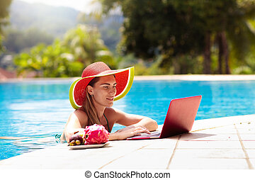 Woman with laptop at swimming pool. Remote work and global nomad concept. Young female freelancer in tropical resort. Conference call and freelance job. Girl in bikini with computer and mobile phone.