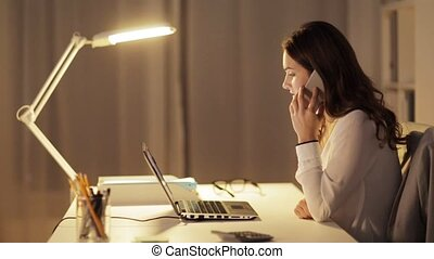 woman with laptop calling on smartphone at office