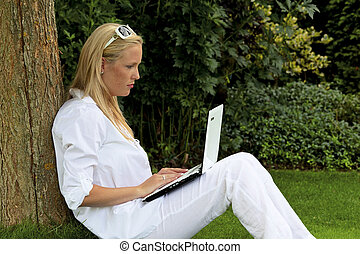 woman with laptop computer in the garden