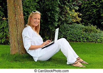 woman with laptop computer in the garden - a young woman...