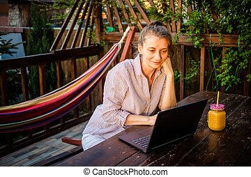 woman with laptop  in backyard  home office