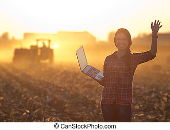 Woman with laptop in front of tractor