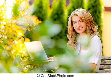 Woman with laptop in garden