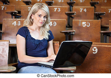Woman with Laptop in Lecture Hall - Portrait of young girl...