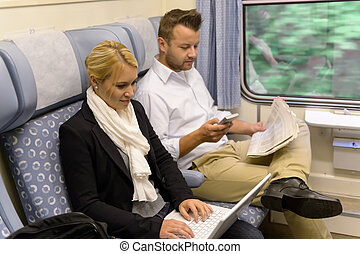 Woman with laptop man newspaper in train