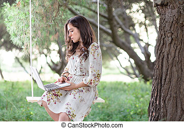 Woman with Laptop on a Swing