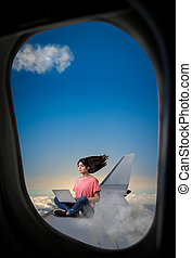 Woman with laptop sitting on plane wing