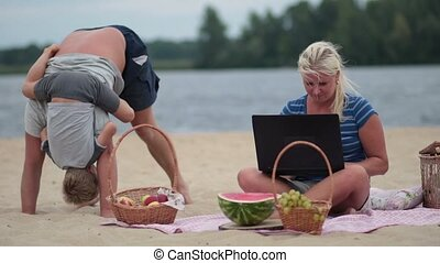Woman with laptop working on the beach