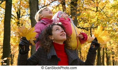 woman with leaves and girls in park