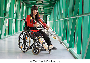 Young woman with leg cast sitting in a wheelchair